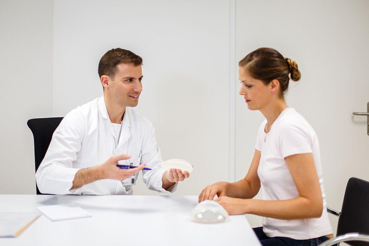 EIn Arzt zeigt einer Patientin verschiedene Brustimplantate