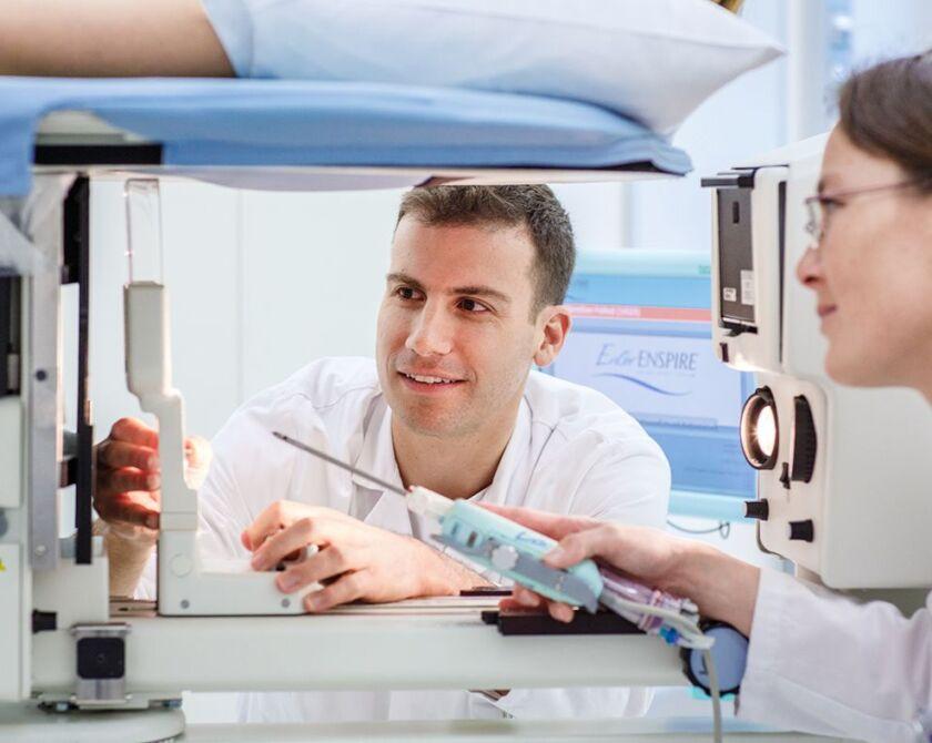 Ein Arzt und eine Ärztin schauen sich zusammen ein Gerät an