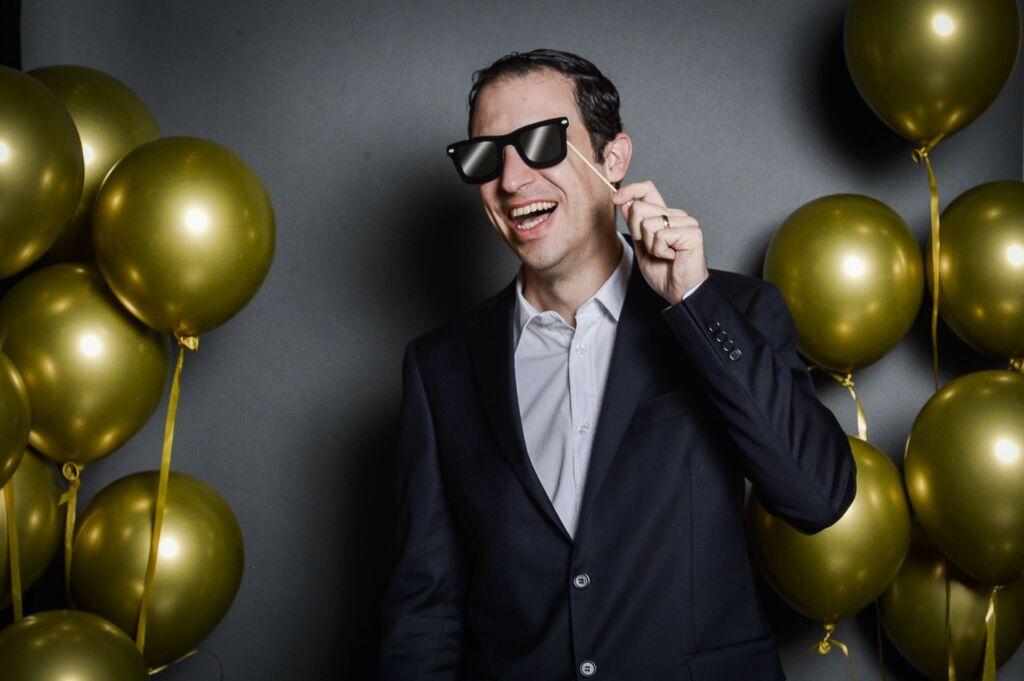 Ein Mann hält eine Sonnenbrille vor sein Gesicht und lacht