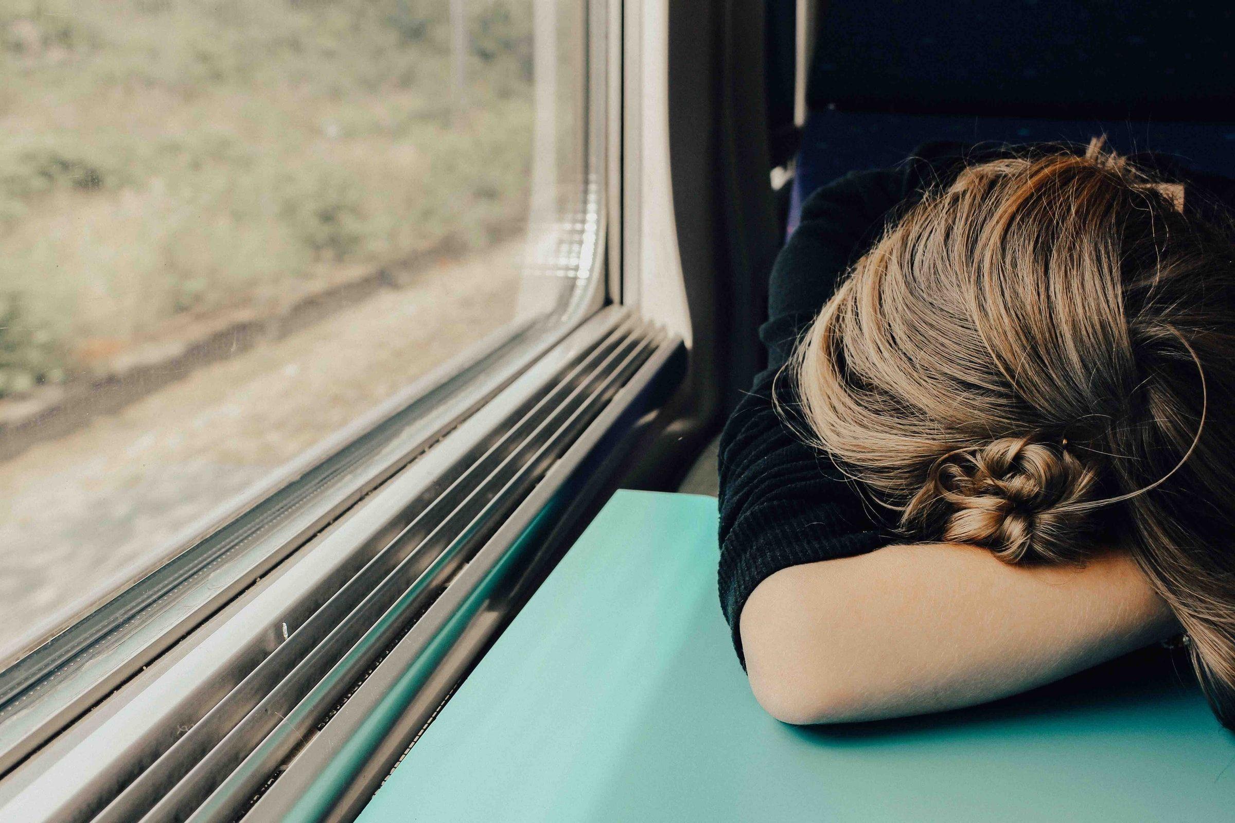 Frau legt ihren Kopf in ihre verschränkten Arme auf einem Tisch in einem Zug