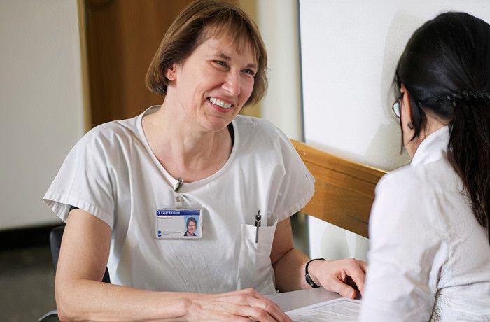 Eine Pflegerin spricht mit einer Patientin
