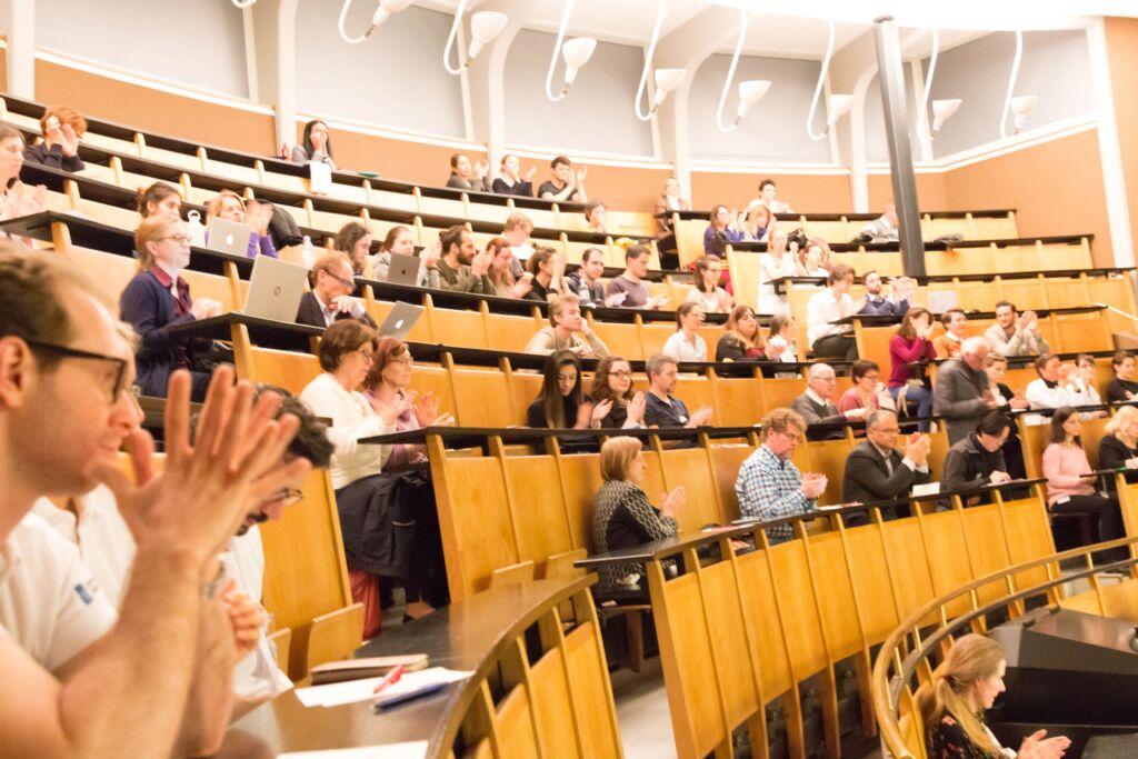 Ein gefüllter Vorlesungssaal in dem die Zuhörenden klatschen