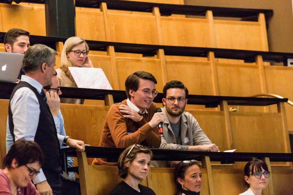 Ein Zuschauer einer Präsentation stellt eine Frage in einem Vorlesungssaal