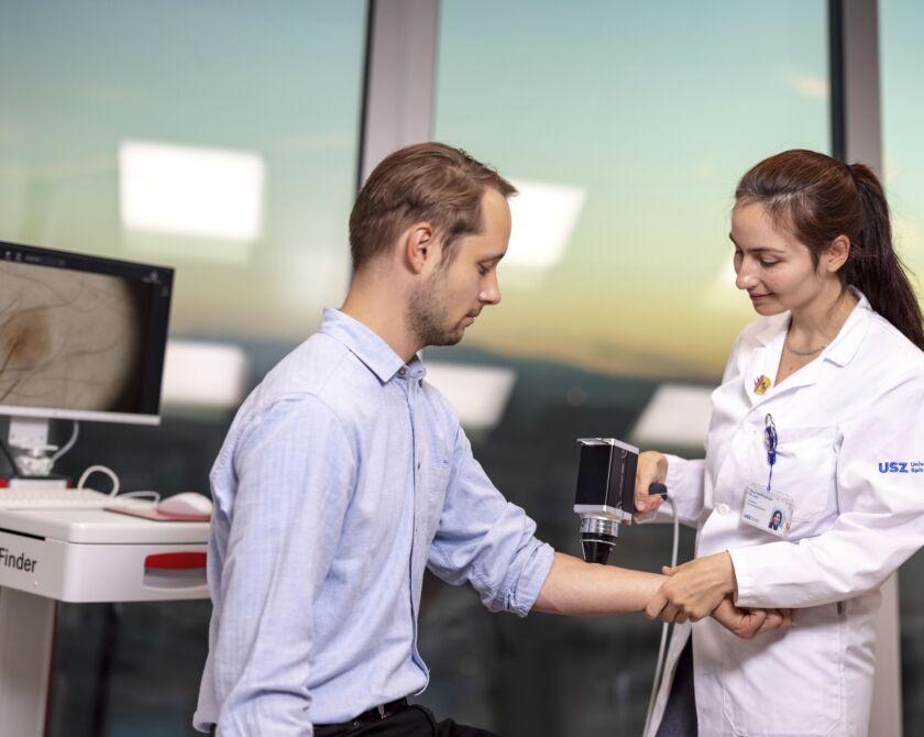 Eine Ärztin untersucht einen Patienten mit einem Auflichtmikroskop.