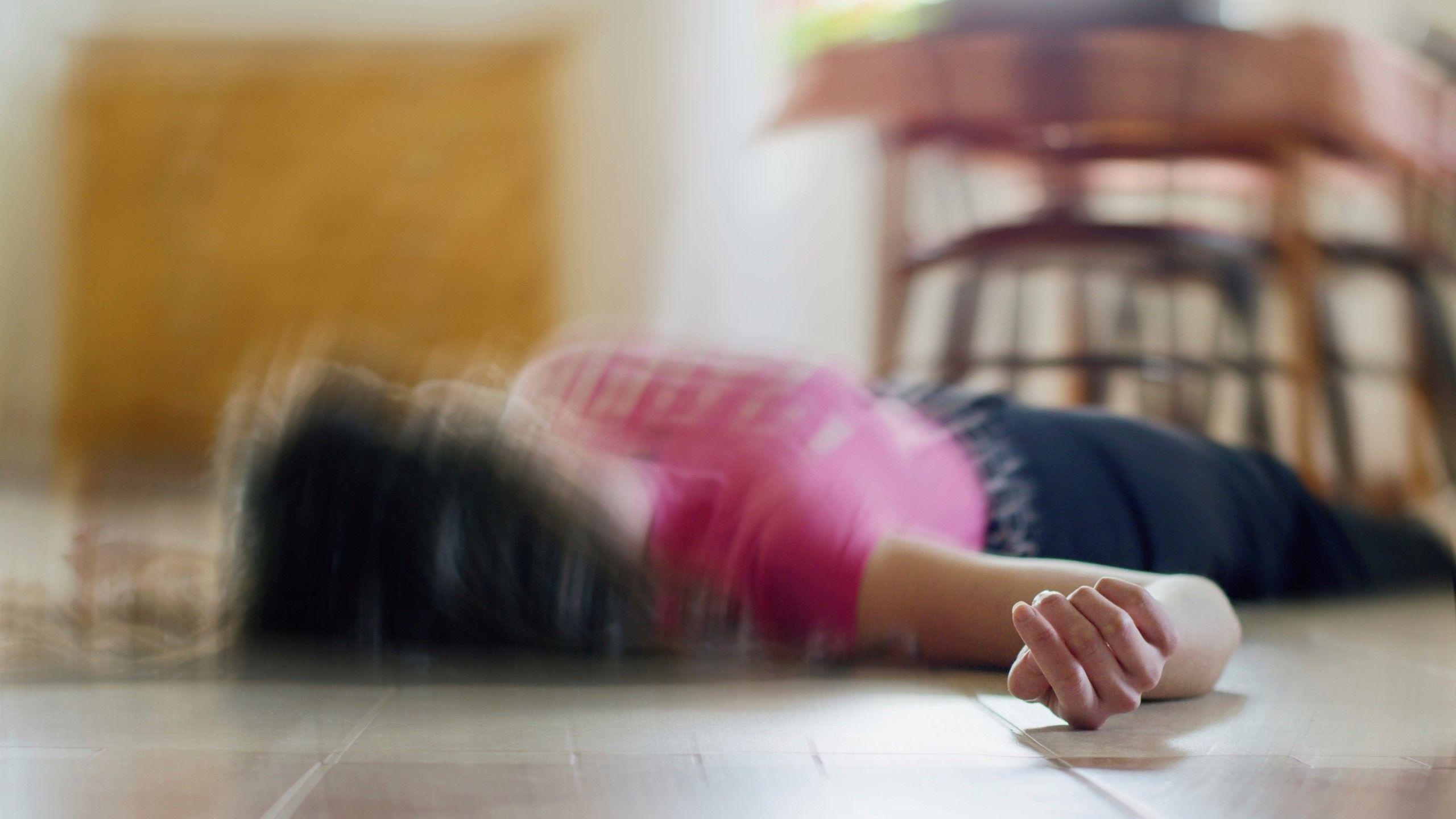 Eine Frau liegt am Boden nach dem sie einen Schlaganfall erlitten hat