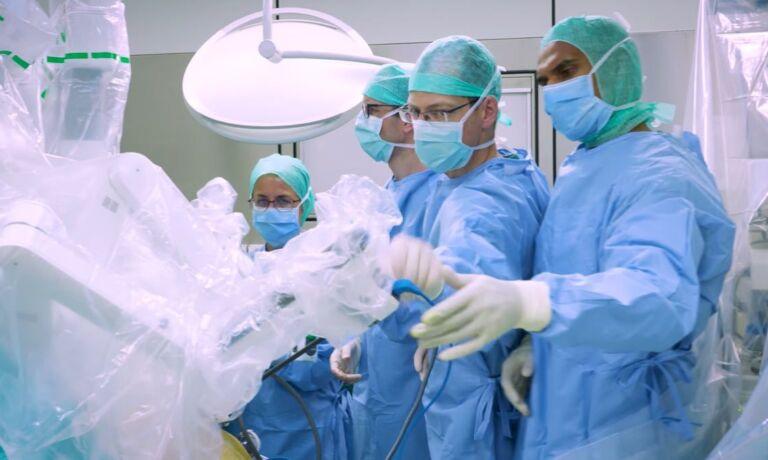 Drei Chirurgen und eine Chirurgin führen eine Darmkrebsoperation durch