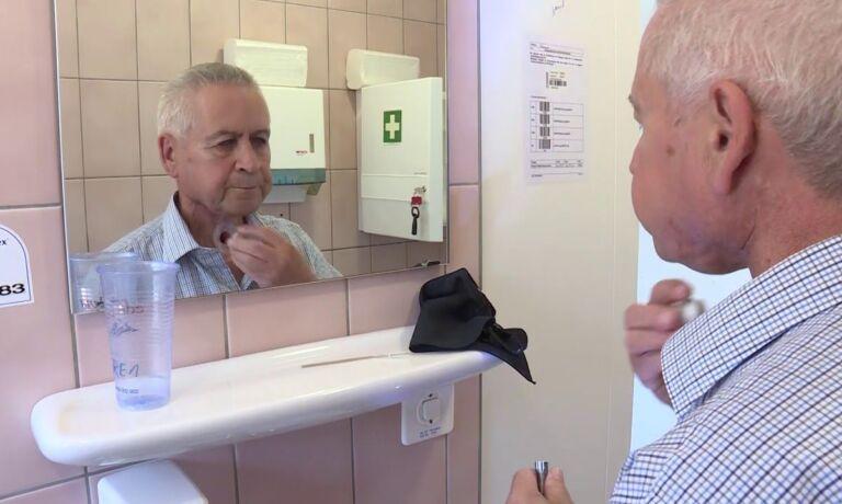 Ein Mann mit einem HNO Karzinom steht vor einem Spiegel