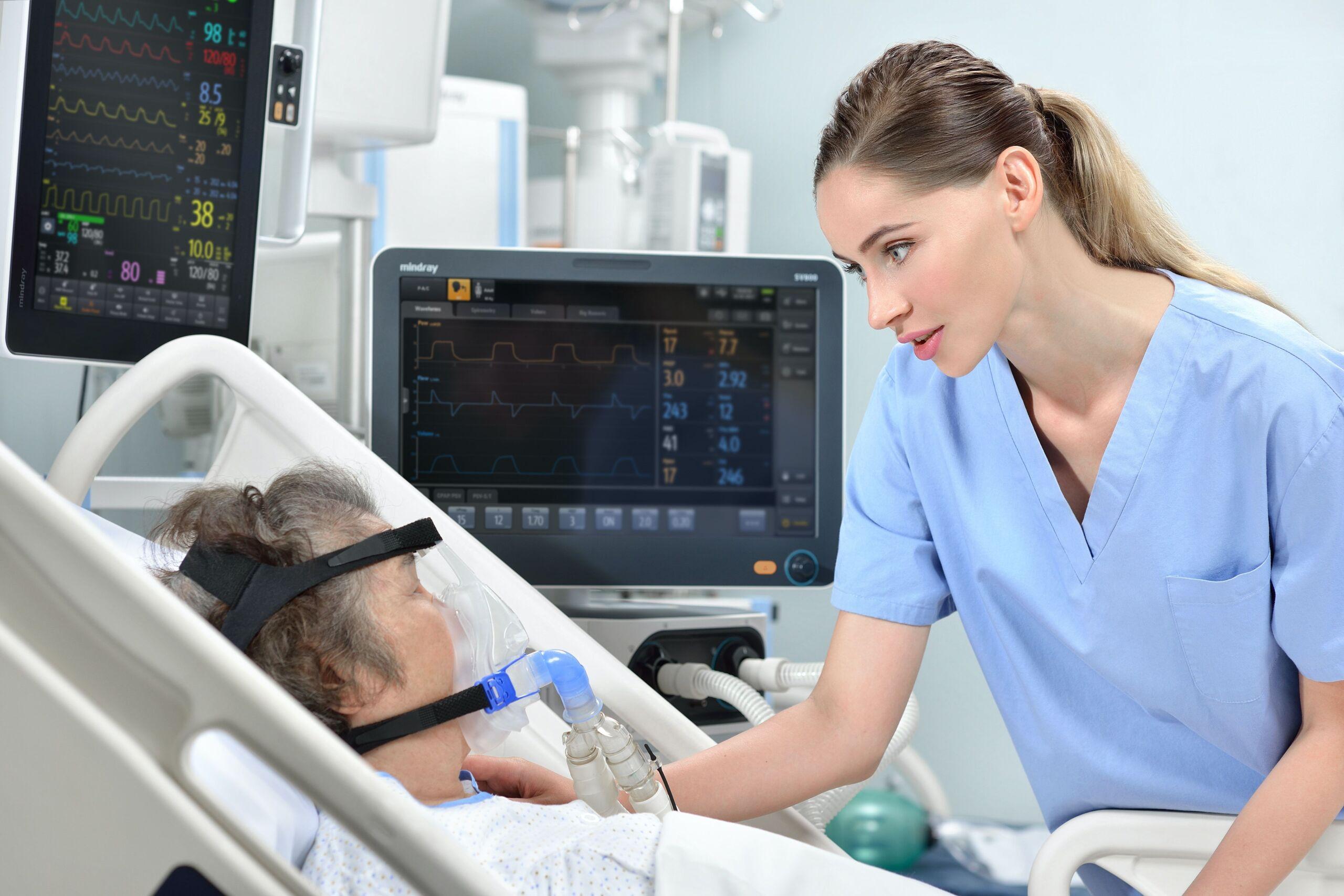 Patientin liegt an einer Beatmungsmaschine und eine Pflegerin schaut nach ihr