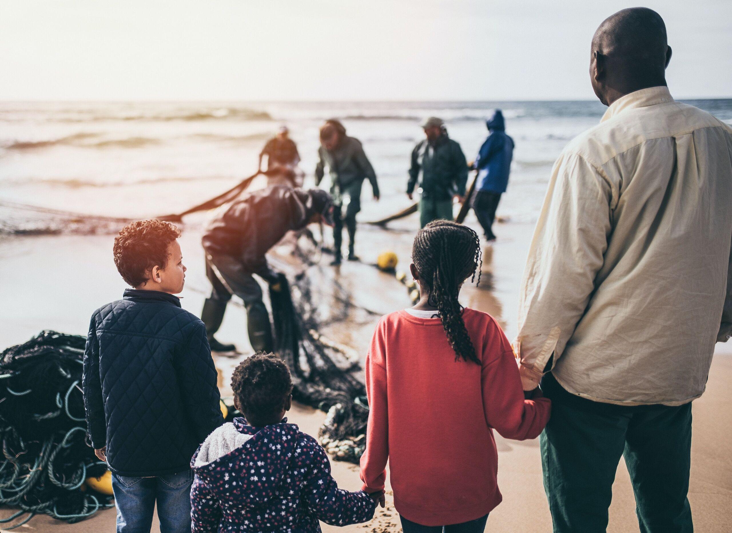 Ein Vater mit seinen drei Kindern steht am Strand und schaut aufs Meer