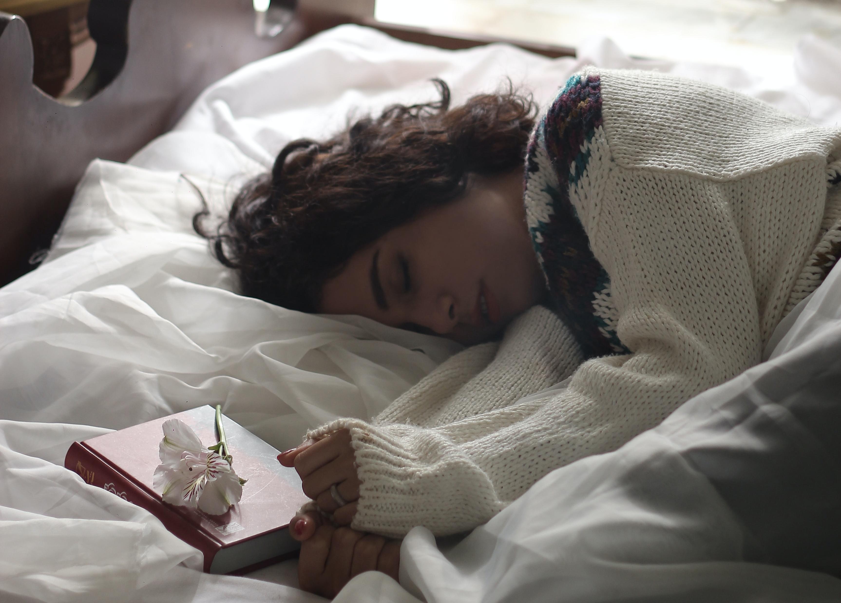 Eine Frau liegt schlafend neben einem Buch