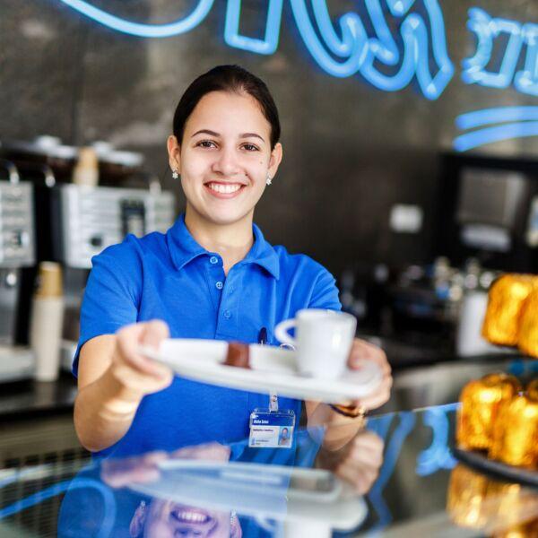 Angestellte mit einem Kaffee in der Hand lächelt in die Kamera