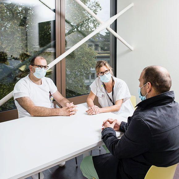 Eine Ärztin und ein Arzt besprechen etwas mit einem Angehörigen
