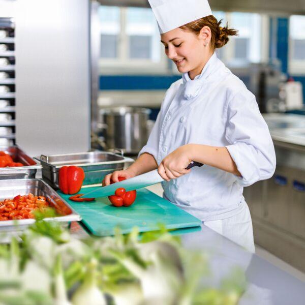 Eine Köchin schneidet mit einem langen Messer eine Paprika