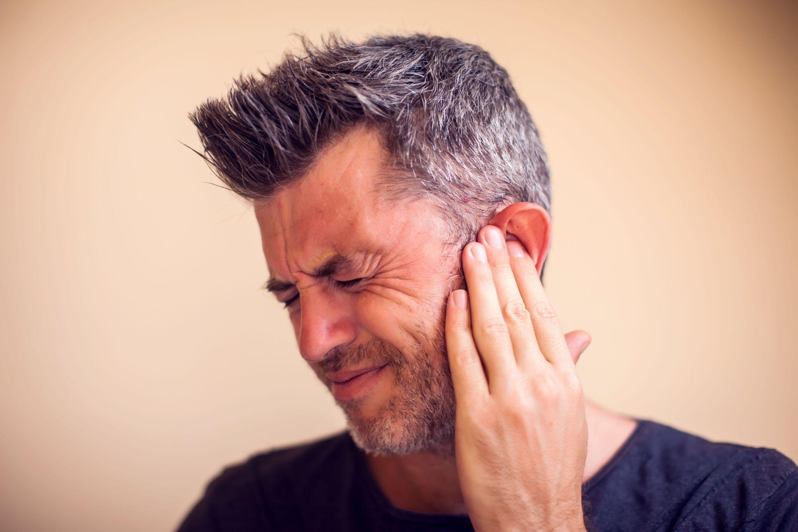 Mann hält sich am Ohr weil es zu schmerzen scheint