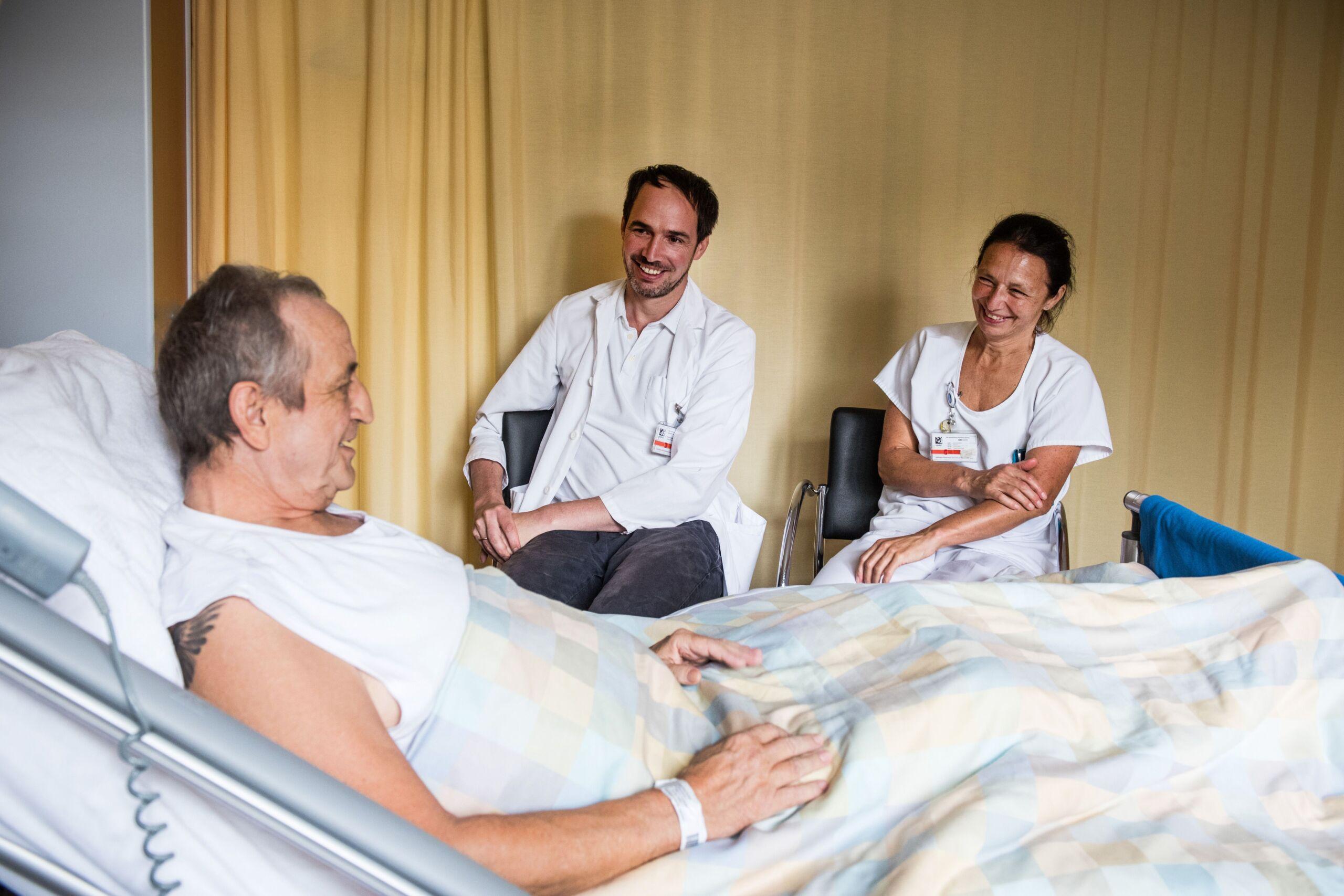 Zwei Pflegende sitzen lächelnd an einem Patientenbett