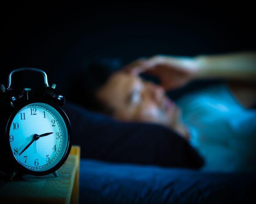 Ein Mann liegt wach im Bett