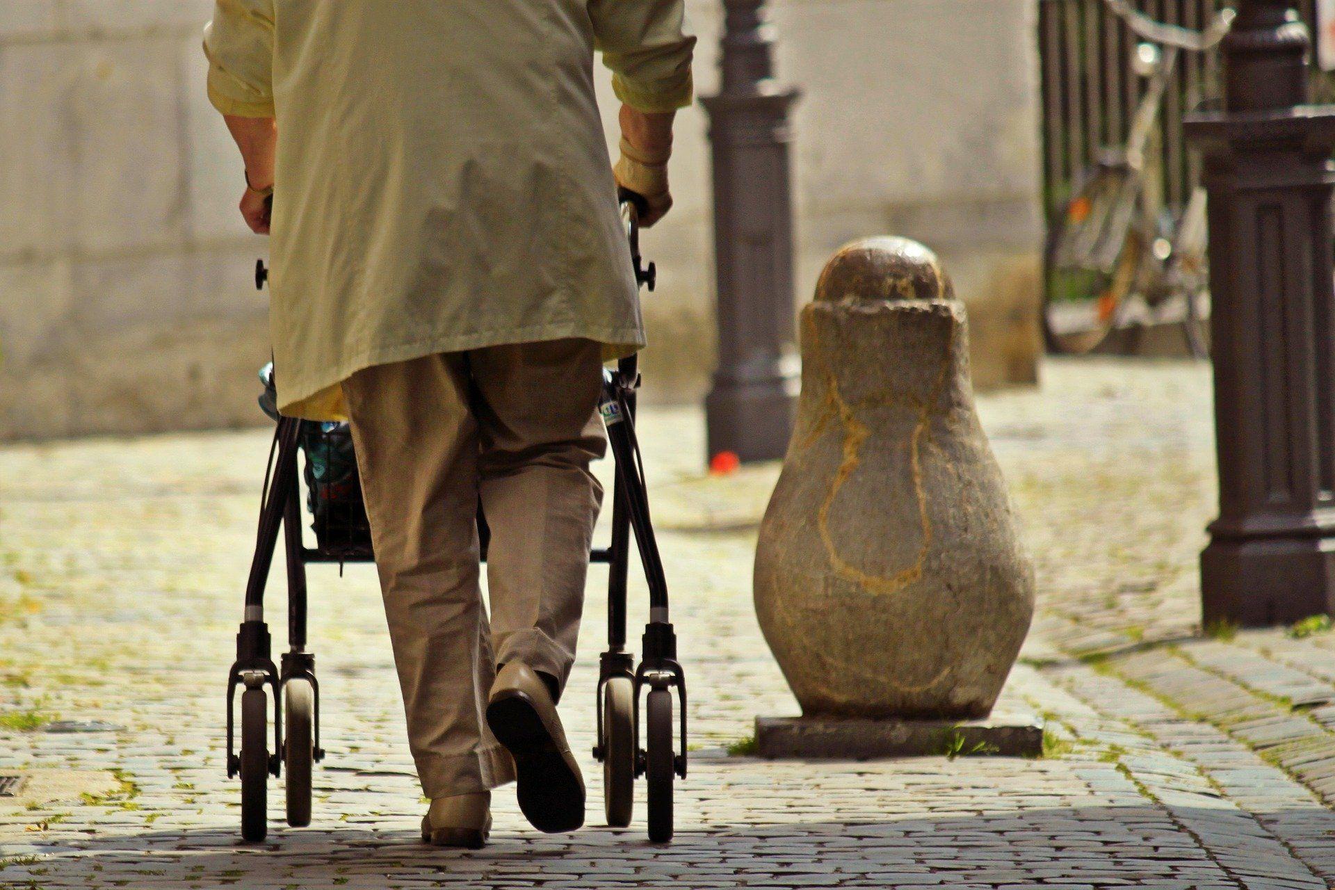 Ältere Frau läuft mit einer Gehhilfe