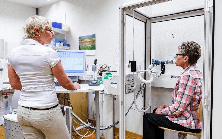 Eine Ärztin führt einen Lungenfunktionstest bei einer Patientin durch