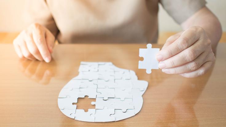 Frau hält Puzzle Teil in der Hand