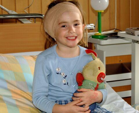 Kind mit Kopfverband lächelt.