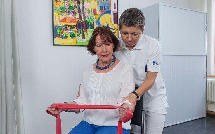 Eine Pflegerin betreut eine sitzende Frau