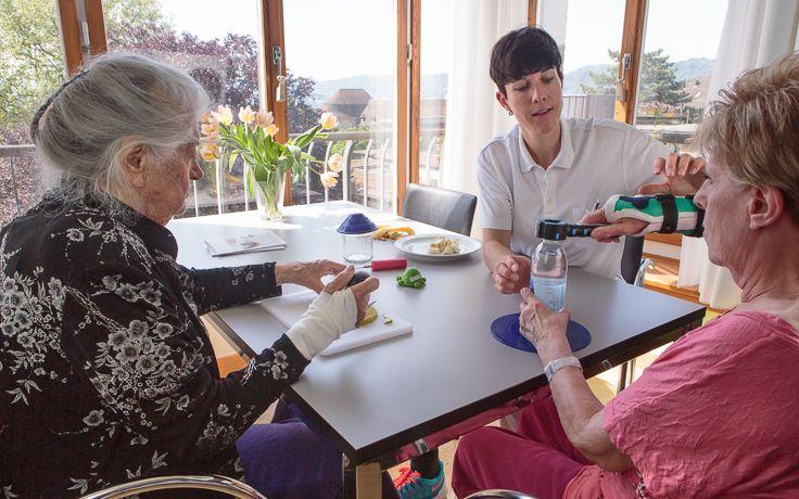 Eine Pflegerin und zwei Patientinnen sitzen an einem Tisch und trinken Wasser