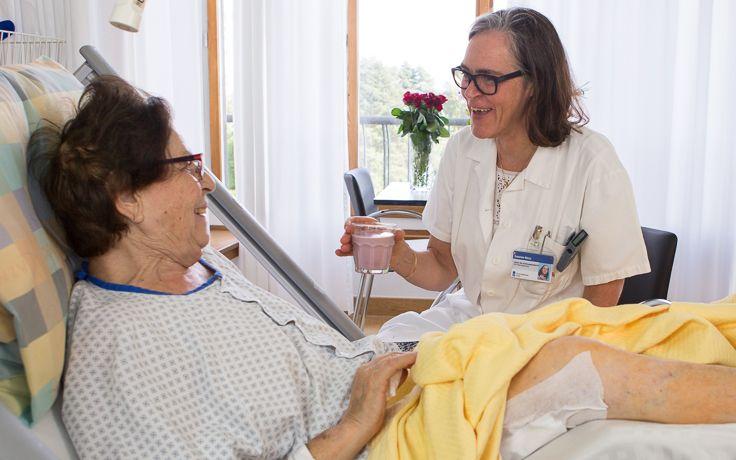 Eine Pflegerin redet mit einer Patientin am Bett