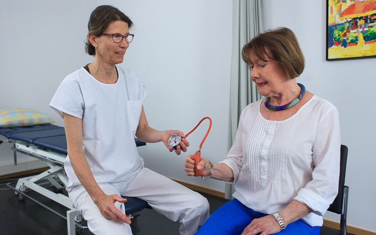 Eine Pflegerin führt einen Test durch bei dem die Griffkraft getestet wird