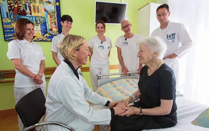 Das Pflegeteam der Geriatrie steht um eine ältere Dame