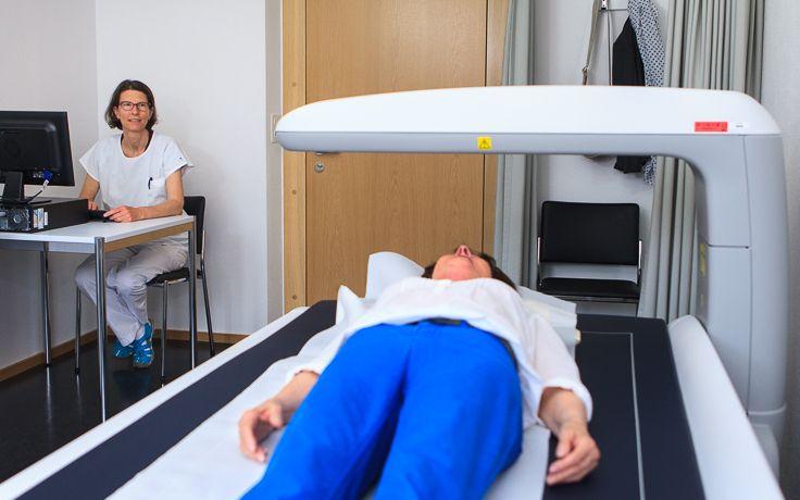 Die Muskelmasse wird mit einem Gerät bei einer Patientin gemessen