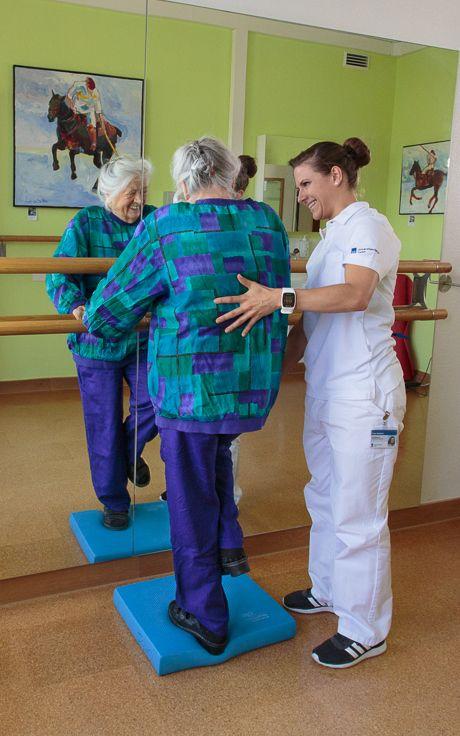 Eine Physiotherapeutin übt das Gleichgewicht zu halten mit einer älteren Dame