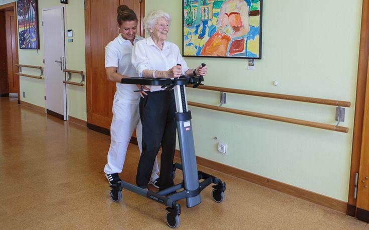 Eine Pflegerin führt ein Gehtraining mit einer älteren Dame durch