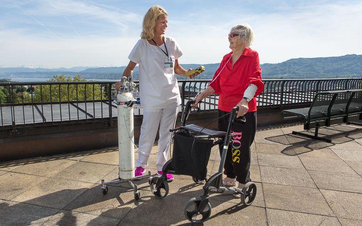 Eine Pflegerin begleitet eine Patientin draussen bei Sonnenschein