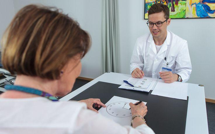 Ein Arzt führt einen Uhrentest bei einer Patientin durch