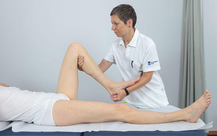 Eine Pflegerin untersucht die Beweglichkeit des Kniegelenks