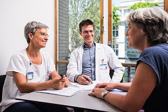 Ein Arzt und eine Pflegerin unterhalten sich an einem Tisch mit einer Patientin