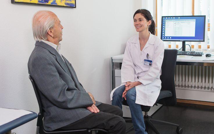 Eine Ärztin befragt einen älteren Patienten