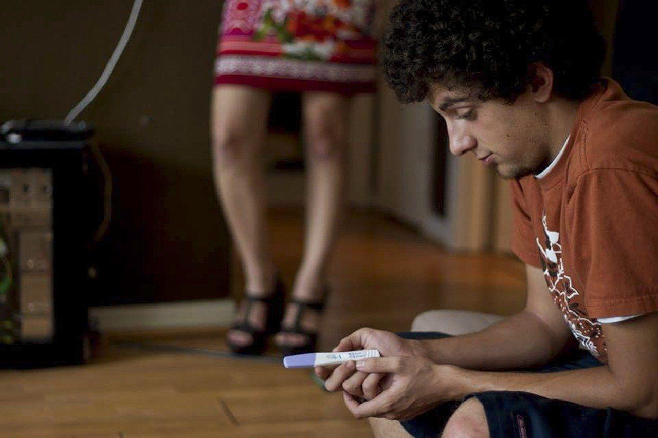 Mann schaut auf Schwangerschaftstest