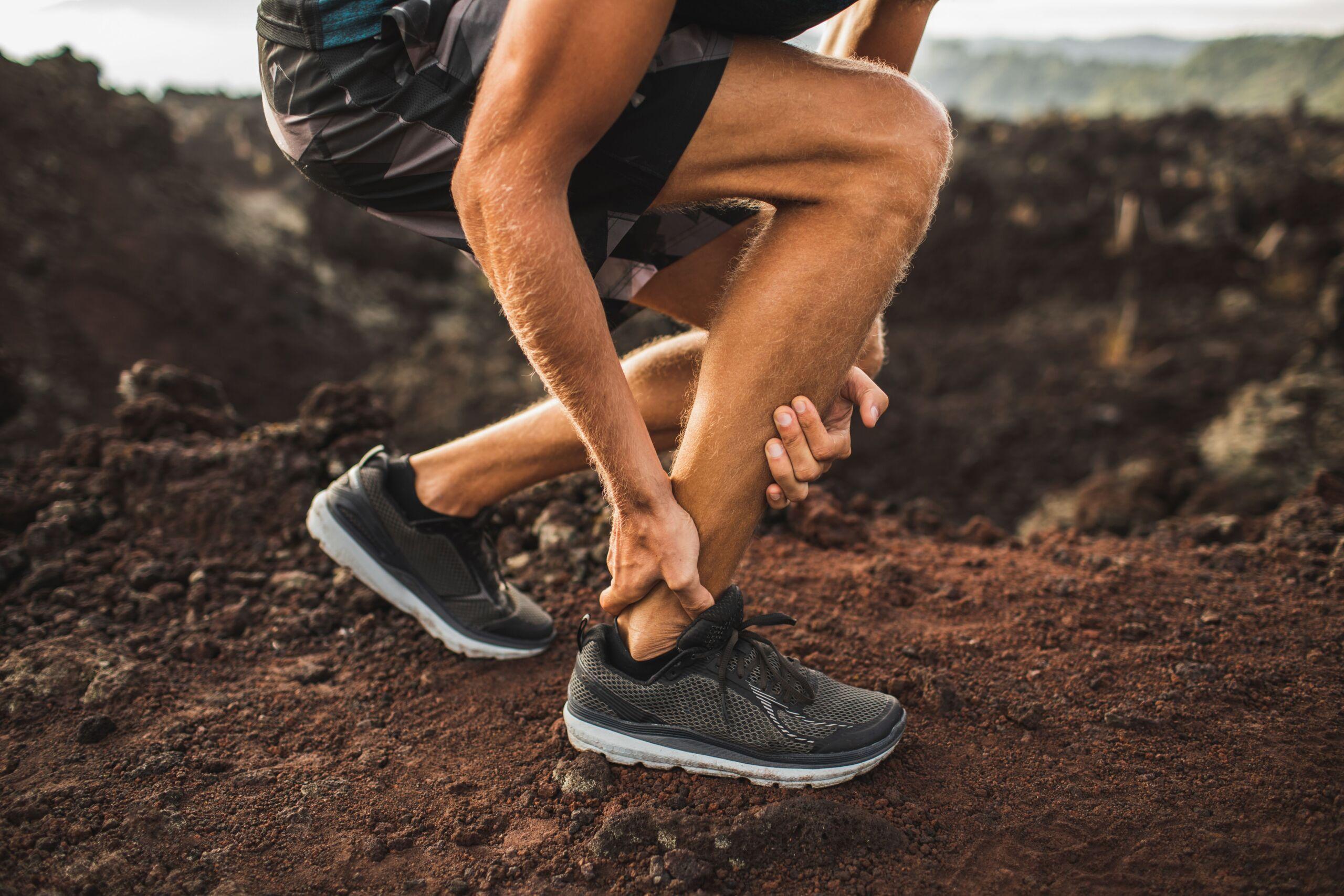Ein Mann hält sich wegen Schmerz die Achillessehne