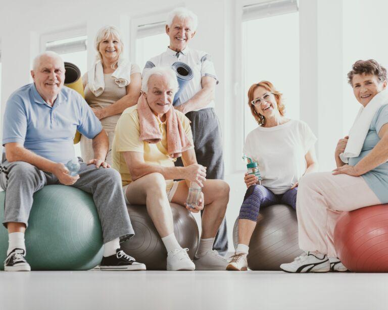 Ältere Personen sitzen auf Gymnastikbällen