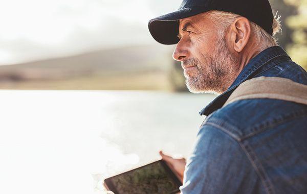 Mann sitzt an einem See und schaut in die Ferne
