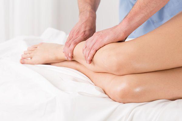 Ein Mann massiert die Beine einer Frau