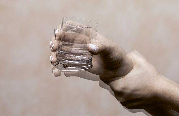 Zitternde Hand, die ein Glas festhält