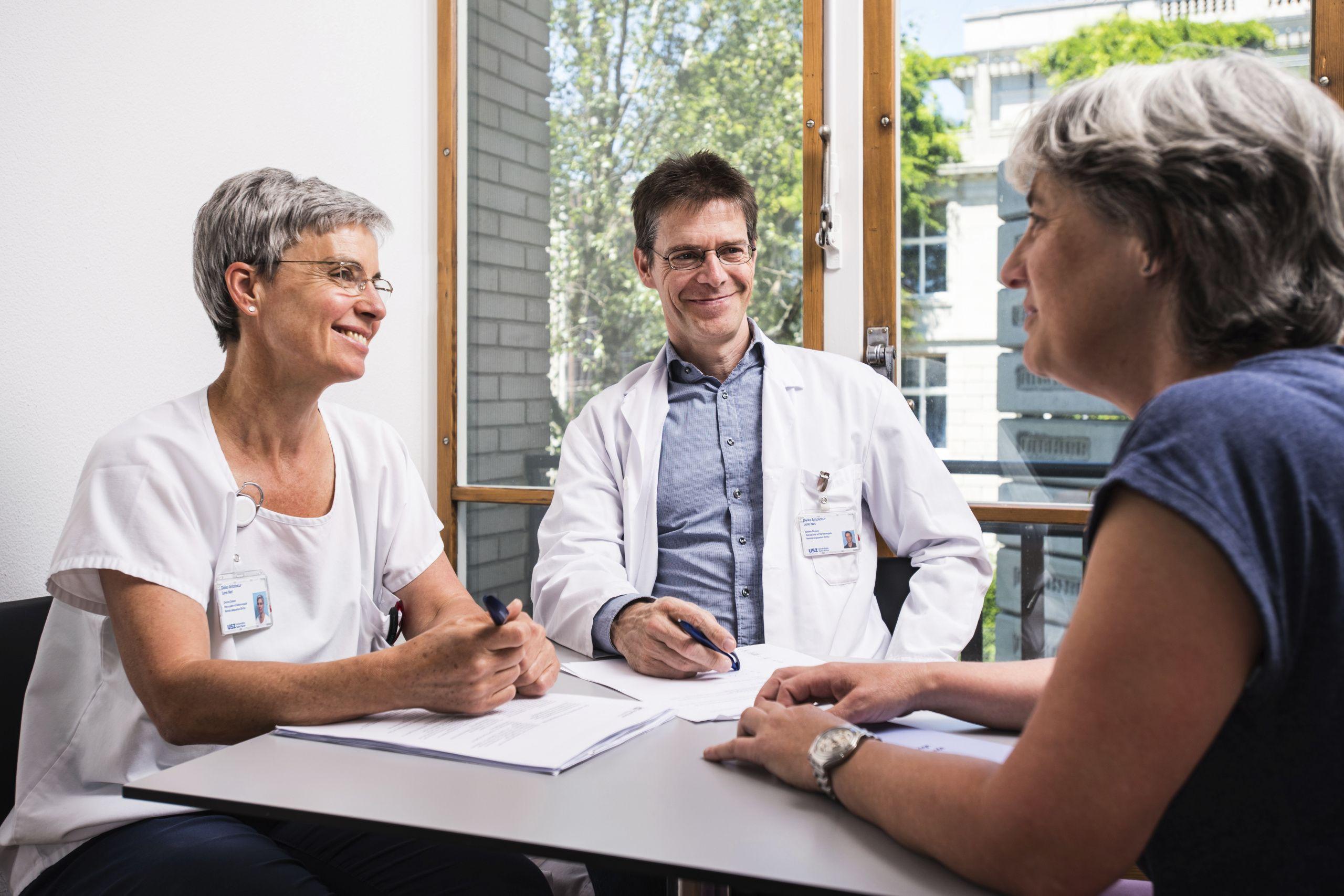 Ein Arzt und eine Pflegeexpertin beraten eine Patientin