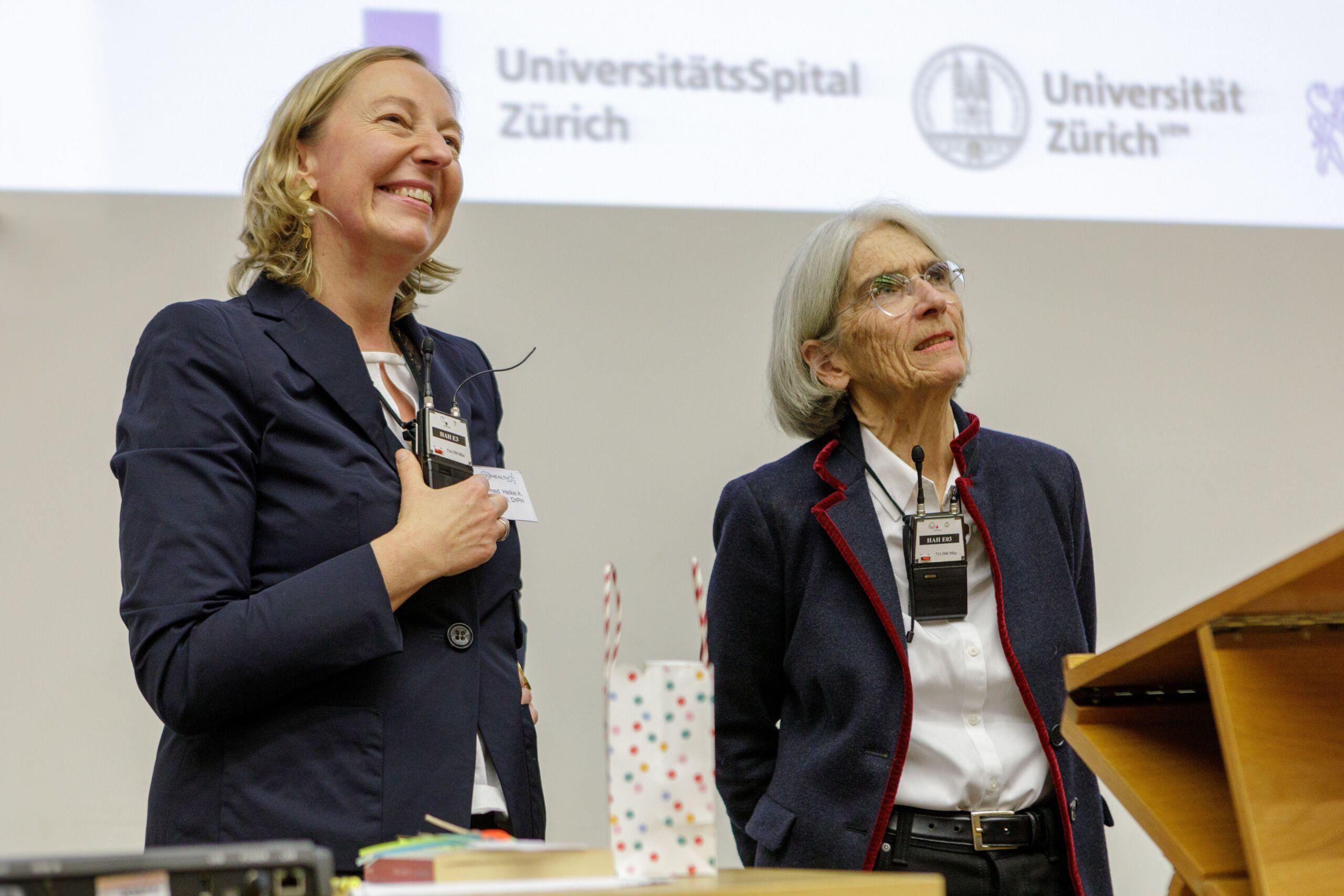 Zwei Frauen lächeln ins Publikum von der Bühne aus.